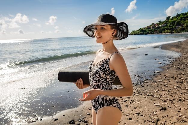 Belle jeune femme en maillot de bain et chapeau va faire du yoga. Photo Premium