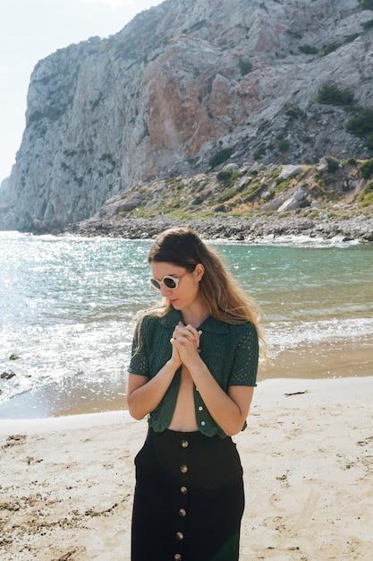 Belle jeune femme avec une main dans la main debout sur la plage Photo gratuit