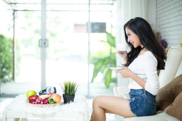 Belle jeune femme à la maison avec un ordinateur portable Photo gratuit