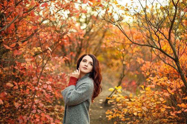 Belle jeune femme en manteau gris nager marchant dans un parc en automne avec des feuilles jaunes et rouges Photo Premium