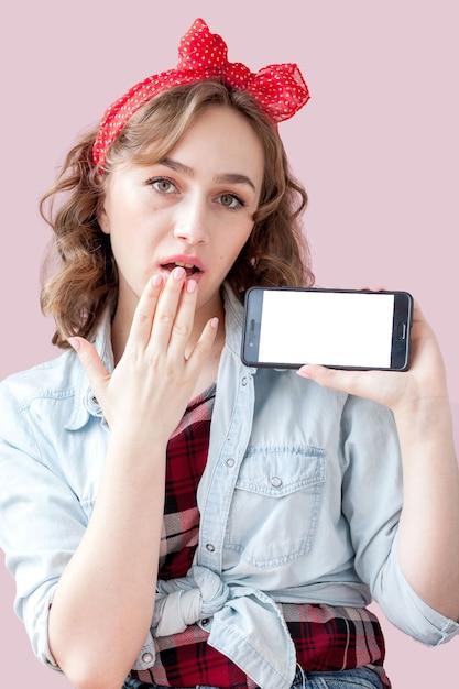 Belle Jeune Femme Avec Maquillage Pin-up Et Coiffure Sur Fond Rose Avec Téléphone Mobile Photo Premium