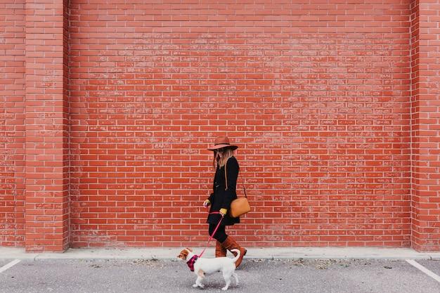 Belle jeune femme marchant avec son chien dans la rue. mur de brique orange amour et animaux domestiques dehors. Photo Premium