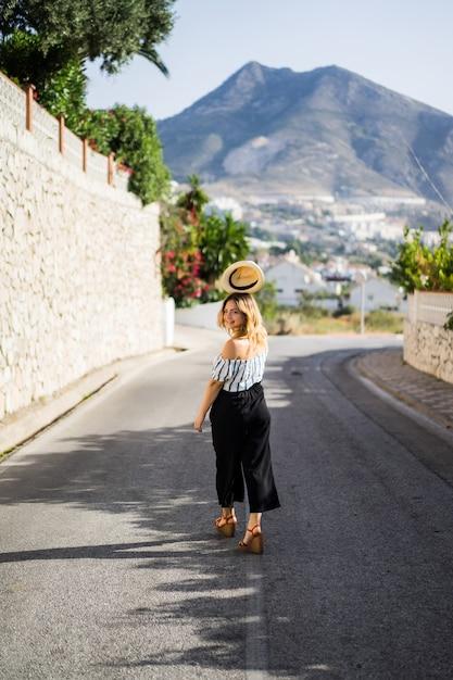 Une belle jeune femme marche dans les rues d'une petite ville européenne. vacances d'été Photo gratuit