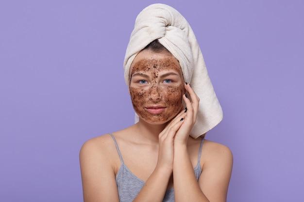 Belle Jeune Femme Avec Masque Au Chocolat Sur Le Visage, Pose Avec Une Serviette Blanche Sur La Tête Photo gratuit
