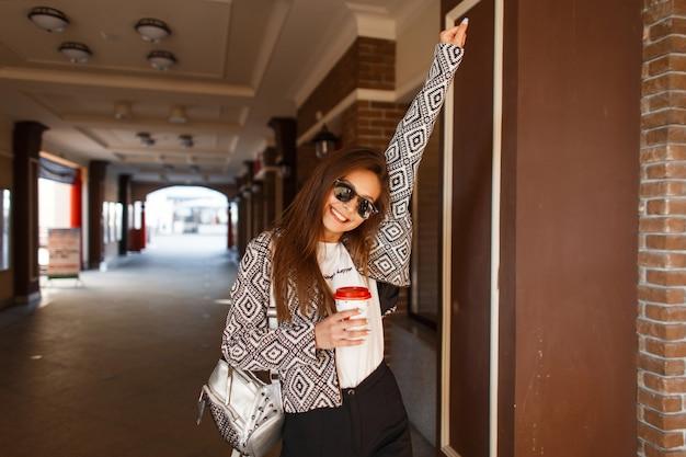 Belle Jeune Femme à La Mode Heureuse Avec Du Café Dans Une Veste élégante Se Promène Dans La Ville Photo Premium