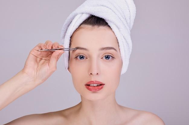 Belle Jeune Femme à Moitié Nue Plumant Des Sourcils Avec Des Pincettes. Photo Premium