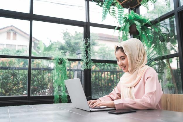 Belle jeune femme musulmane asiatique souriante travaillant sur un ordinateur portable assis dans le salon à la maison Photo gratuit