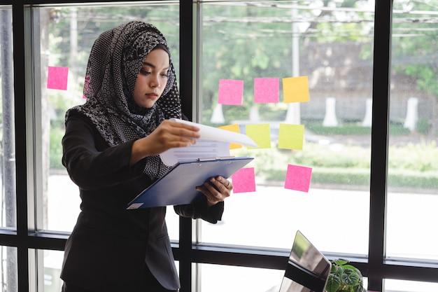 Belle jeune femme musulmane lisant le document de rapport commercial devant le bureau de mur de verre. Photo Premium