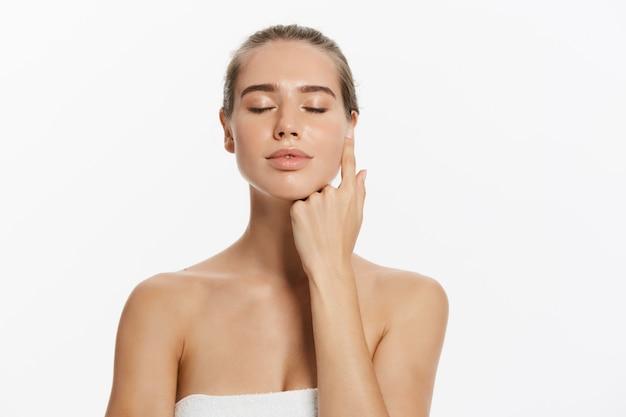 Belle jeune femme à la peau douce et propre touche son propre visage. traitement facial. Photo Premium