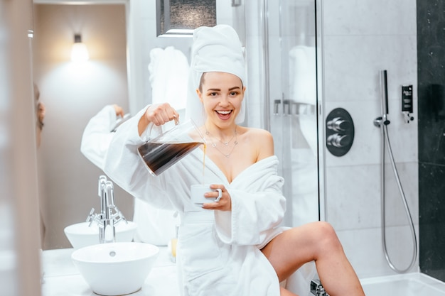 Belle Jeune Femme En Peignoir Et Serviette Sur La Tête, Assise Sur Une Baignoire Photo gratuit