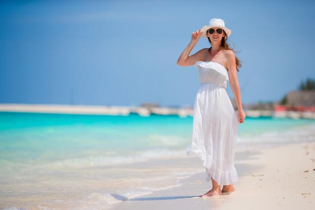 Belle jeune femme pendant les vacances à la plage tropicale. bonne fille en robe blanche profiter de ses vacances d'été Photo Premium