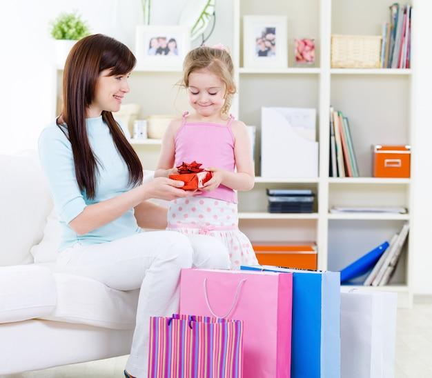 Belle Jeune Femme Et Petite Fille Avec Un Cadeau Après Avoir Acheté à La Maison Photo gratuit