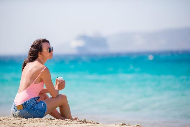 Belle jeune femme sur la plage en europe. fille avec café en vacances à mykonos, grèce Photo Premium