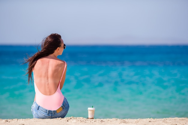 Belle jeune femme sur la plage pendant les vacances tropicales. fille boire un café froid sur l'une des belles plages de mykonos, en grèce, en europe. Photo Premium