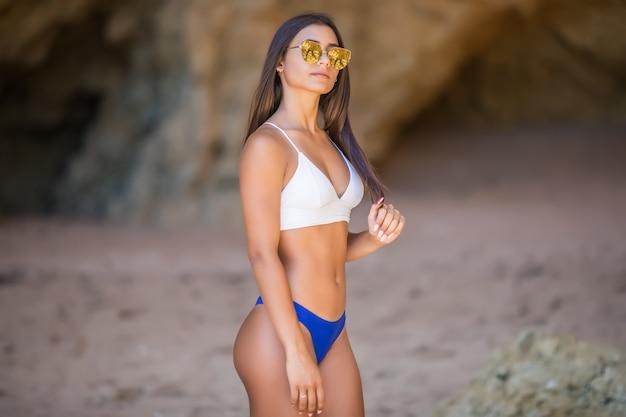 Belle Jeune Femme à La Plage En Regardant La Caméra. Heureuse Fille Latine En Bikini Blanc Souriant. Photo gratuit