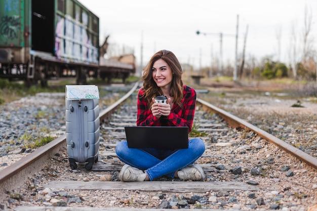 Belle jeune femme portant des vêtements décontractés, assise sur le chemin de fer avec valise, ordinateur portable et une carte, elle sourit et tient une tasse de café. mode de vie en plein air. concept de voyage. Photo Premium