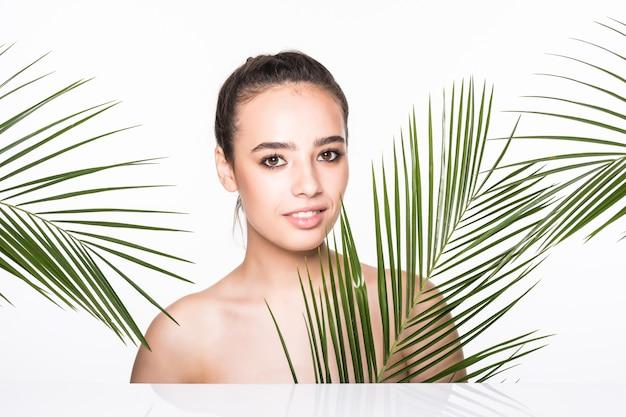 Belle Jeune Femme Posant Avec Des Feuilles De Palmier Vert Photo gratuit