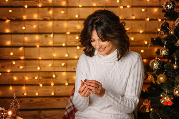 Belle jeune femme près de l'arbre de noël dans un pull blanc Photo Premium