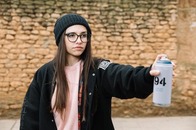 Belle jeune femme pulvérisation d'aérosol peut se tenir devant le mur de pierre Photo gratuit