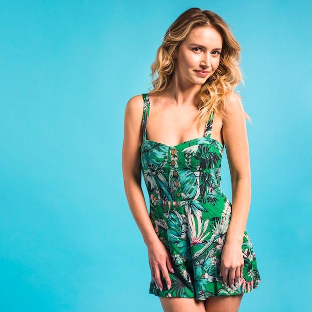 Belle jeune femme qui pose en robe à fleurs Photo gratuit