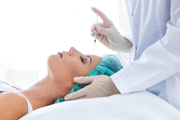 Belle jeune femme recevant une injection cosmétique de botox dans son visage. Photo gratuit