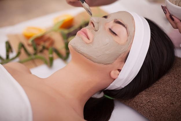Belle jeune femme recevant un masque facial gris dans le salon de beauté Photo Premium