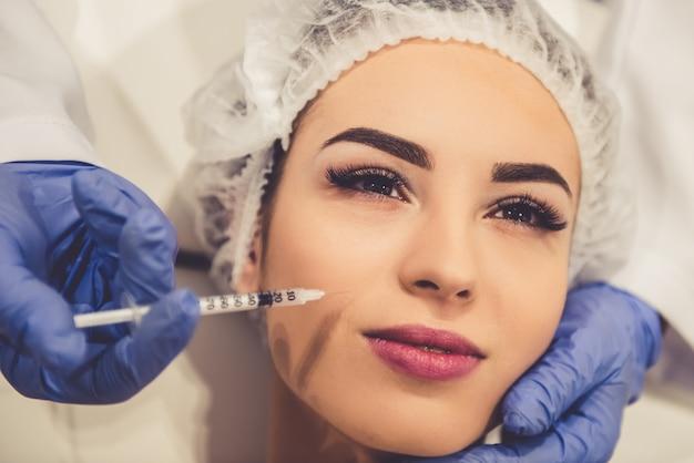 Belle jeune femme reçoit une injection au visage. Photo Premium