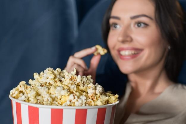 Belle jeune femme en regardant un film au cinéma Photo Premium