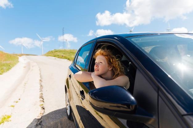 Belle jeune femme regardant par la fenêtre de la voiture Photo gratuit