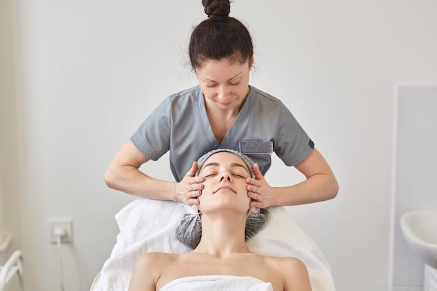 Belle Jeune Femme Relaxante Avec Massage Du Visage Au Spa De Beauté En Position Couchée Photo gratuit