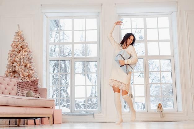 Belle Jeune Femme En Robe Blanche Posant Avec Boîte-cadeau Photo gratuit