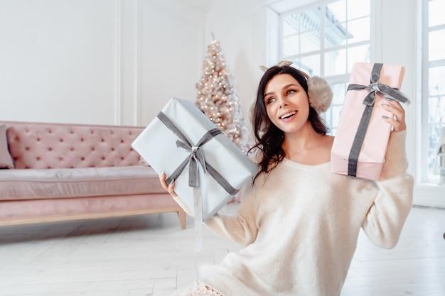Belle Jeune Femme En Robe Blanche Posant Avec Des Coffrets Cadeaux Photo gratuit