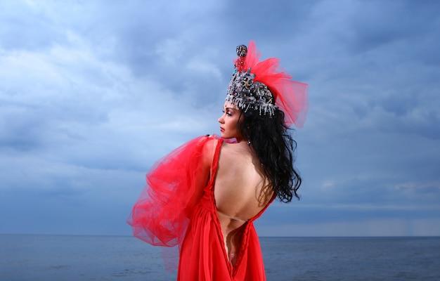 Belle Jeune Femme En Robe Longue Rouge Près De La Mer Photo gratuit