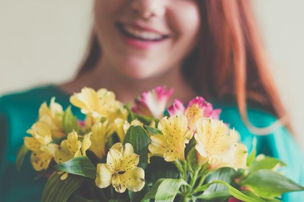 Belle jeune femme en robe verte tenant un bouquet de fleurs de printemps Photo Premium