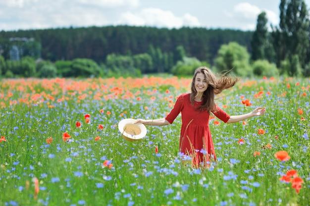Belle jeune femme romantique au chapeau de paille sur le champ de fleurs de pavot Photo Premium