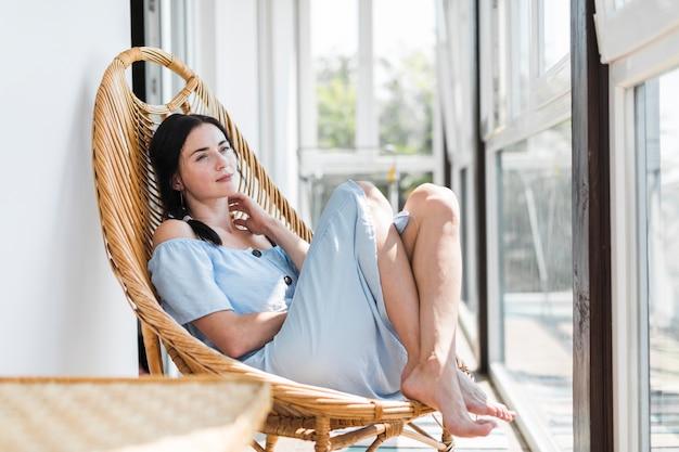 Belle jeune femme se détendre sur une chaise en bois au patio Photo gratuit
