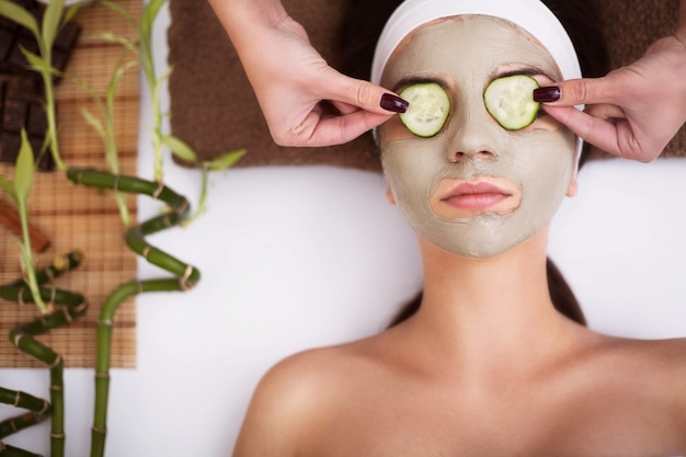 Belle jeune femme se masque facial d'argile au spa Photo Premium