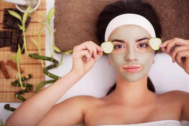 Belle jeune femme se masque facial d'argile au spa Photo Premium