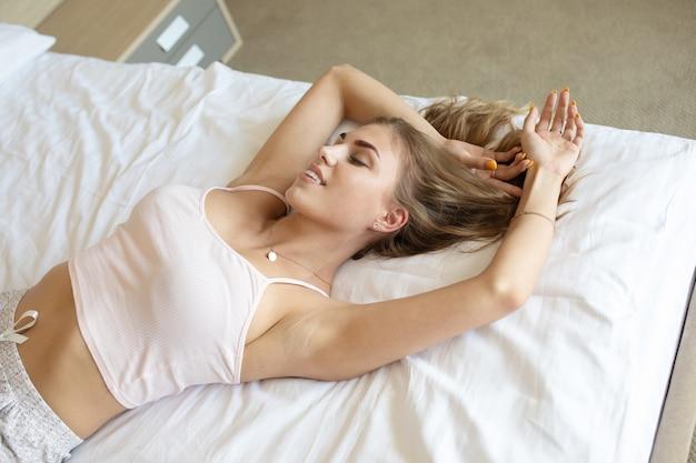 Belle Jeune Femme Se Réveillant Dans Son Lit Entièrement Reposé. Photo Premium