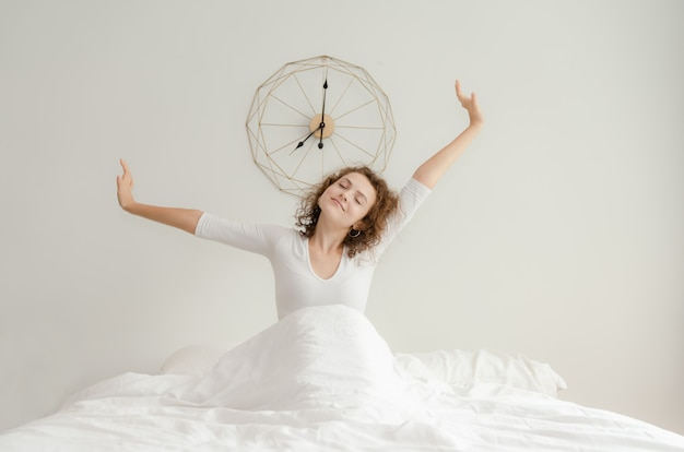 Belle jeune femme se réveiller et s'étirer dans son lit le matin Photo Premium