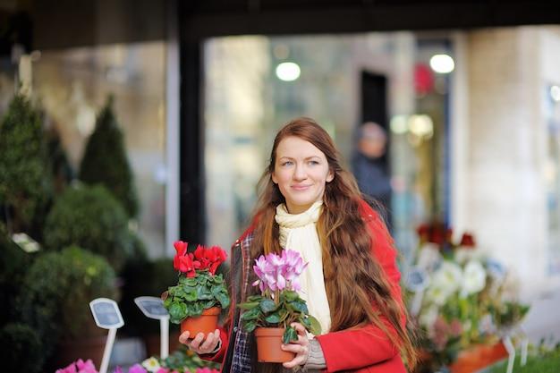 Belle jeune femme en sélectionnant des fleurs fraîches au marché parisien Photo Premium