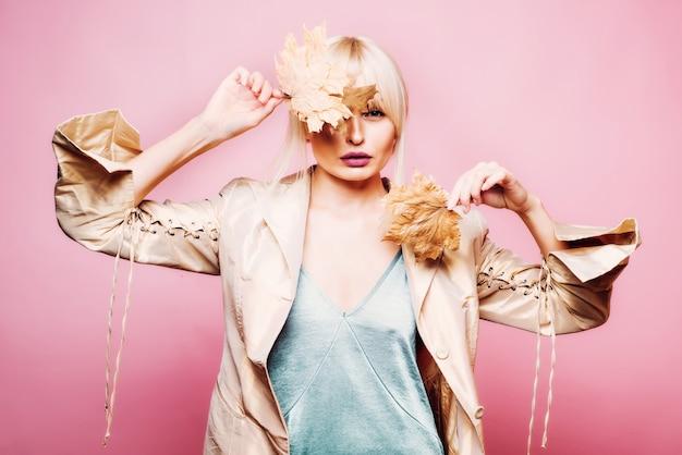 Belle Jeune Femme Sexy Se Trouve Sur Fond De Bois. Jolie Jeune Femme Dans Un Vêtement Saisonnier Avec Feuille D'or. Photo Premium