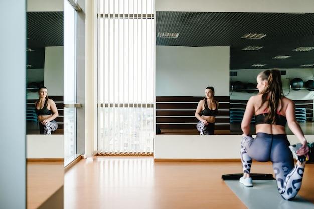 Belle Jeune Femme Sexy En Tenue De Sport Faisant Des étirements Flexibles De Ses Jambes, Sur Le Sol Sur Un Tapis Dans Une Salle De Sport Devant Le Miroir Photo Premium