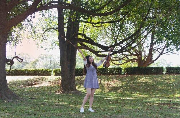 Belle Jeune Femme Soulève Le Violon Et S'incline, Avec Un Sentiment De Bonheur, Portrait De Modèle Posant, Dans Un Parc, Reflet De La Lumière Du Soleil Qui Brille Autour Photo Premium