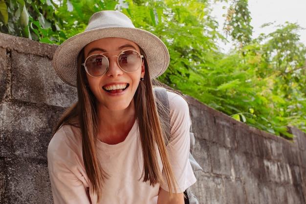 Belle jeune femme souriante à lunettes près des plantes Photo Premium