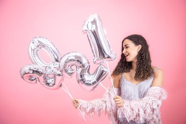 Belle Jeune Femme Souriante Sur Un Mur Rose Avec Des Ballons D'argent Pour Le Concept De Nouvel An Photo Premium