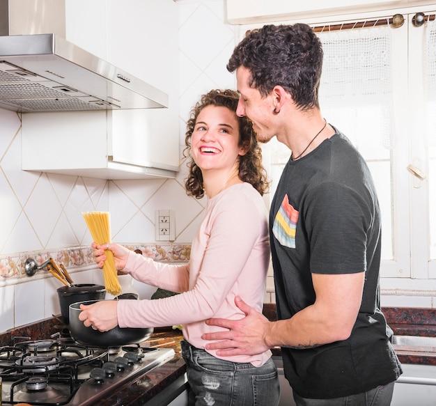 Belle jeune femme souriante prépare des spaghettis en regardant son mari Photo gratuit