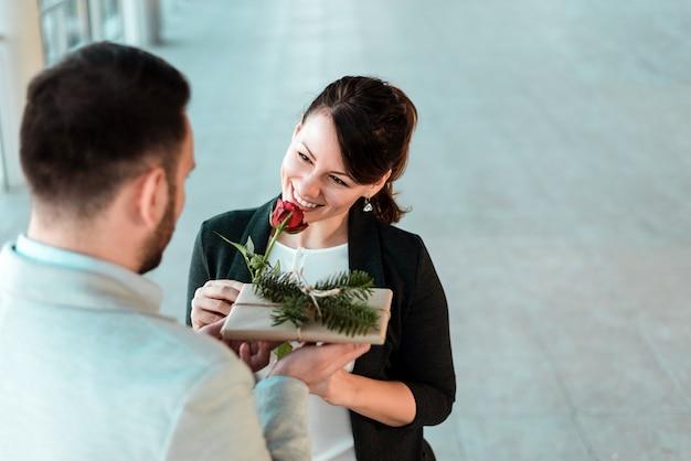 Belle jeune femme souriante recevant la rose et un cadeau de son petit ami. Photo Premium