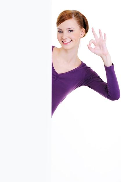 La Belle Jeune Femme Souriante Regarde à Cause D'une Bannière Publicitaire Blanche Vierge Avec Un Geste Correct Photo gratuit