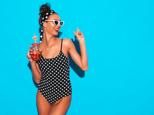 Belle Jeune Femme Souriante Sexy Hipster En Lunettes De Soleil.fille En Maillot De Bain Pois D'été Maillot De Bain.poser Près Du Mur Bleu, Boire Un Cocktail De Boisson Fraîche. Photo gratuit